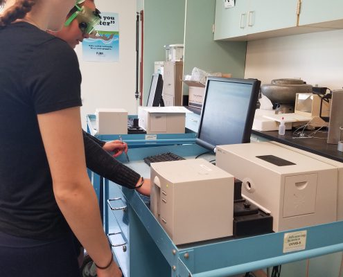 CBNA students Lindsay Wright (Right), Sydney Ho-Sue (Left) work with a spectrometer on loan from the University of New Hampshire