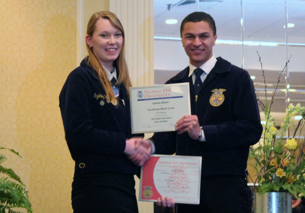 CBNA senior Sydney M. Wilson (left) the 2016 recipient of the DEKALB Agricultural Accomplishment Award receiving her State FFA Degree and State Star Farmer Award in April of 2016.  Presenting the award is Manny Catala, State Parliamentarian.